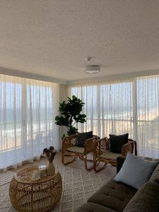 Curtained windows of a beach front flat, the photo contains a plant, two wicker chairs, wicker coffee table, couch