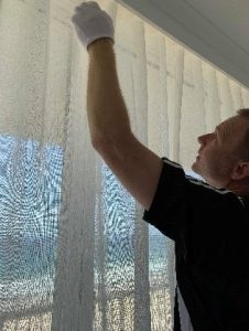 A Blindo window furnishing specialist installing curtains in the windows.