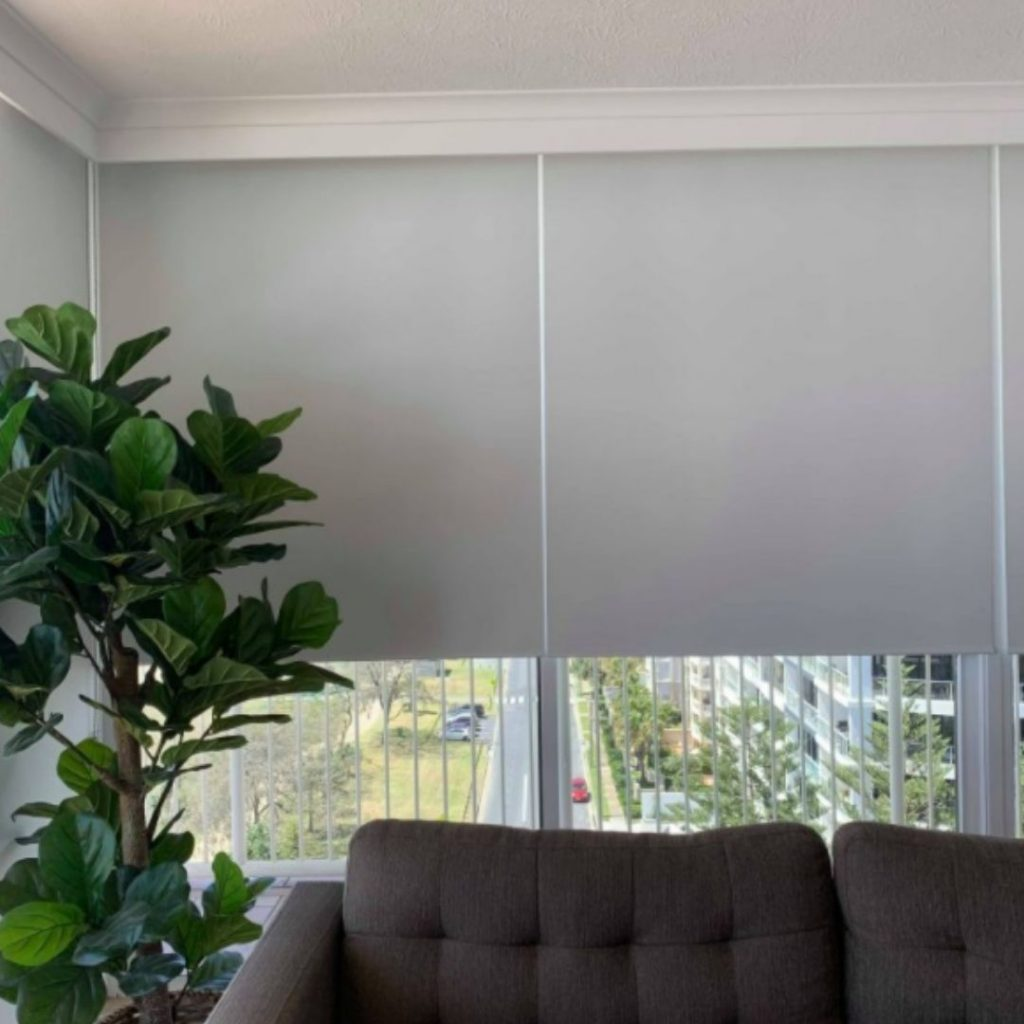 Partially lowered blinds above a couch - best window coverings to keep the heat out blog featured image