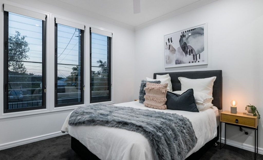 A modern bedroom in the evening with a lit table lamp and large venetian blinds in the window