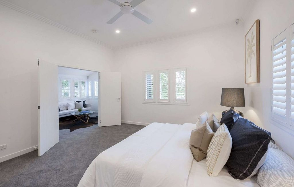 A bedroom with shutters in the windows