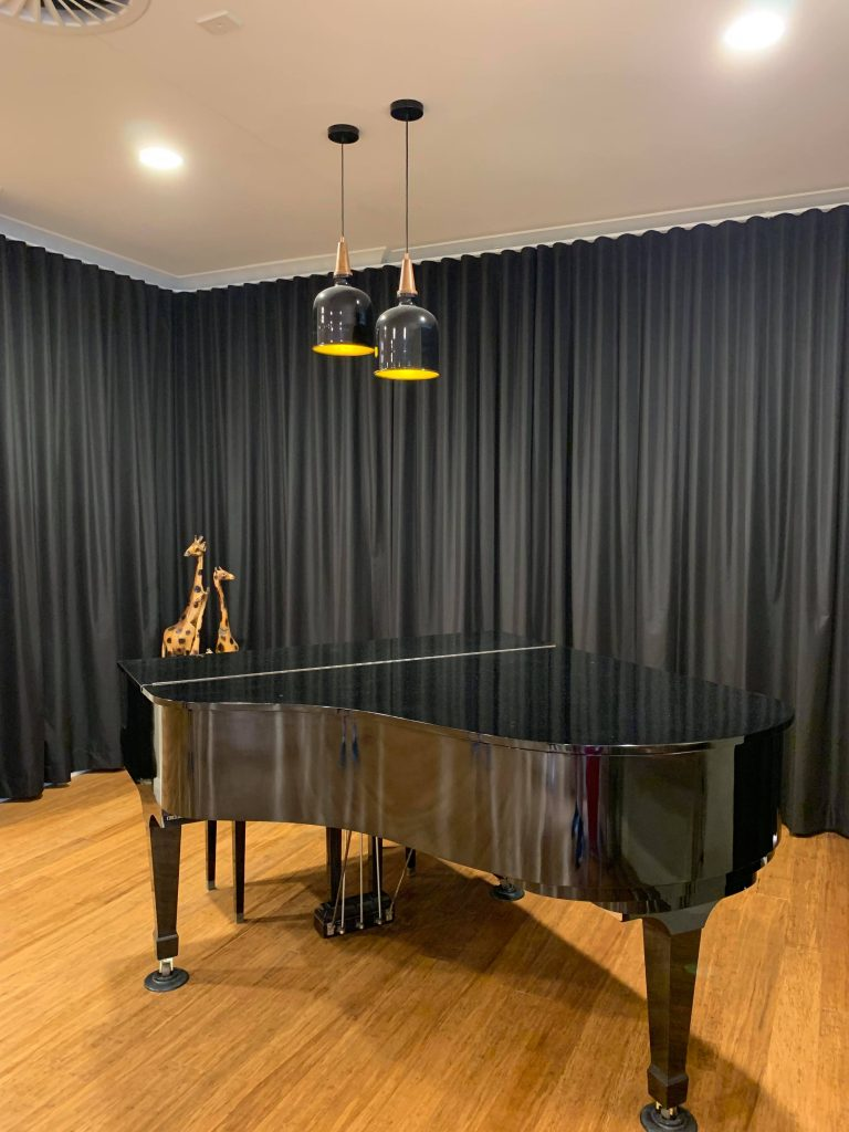 A black baby grand piano in a game room with heavy dark curtains | Game Room Curtains Blog Featured Image