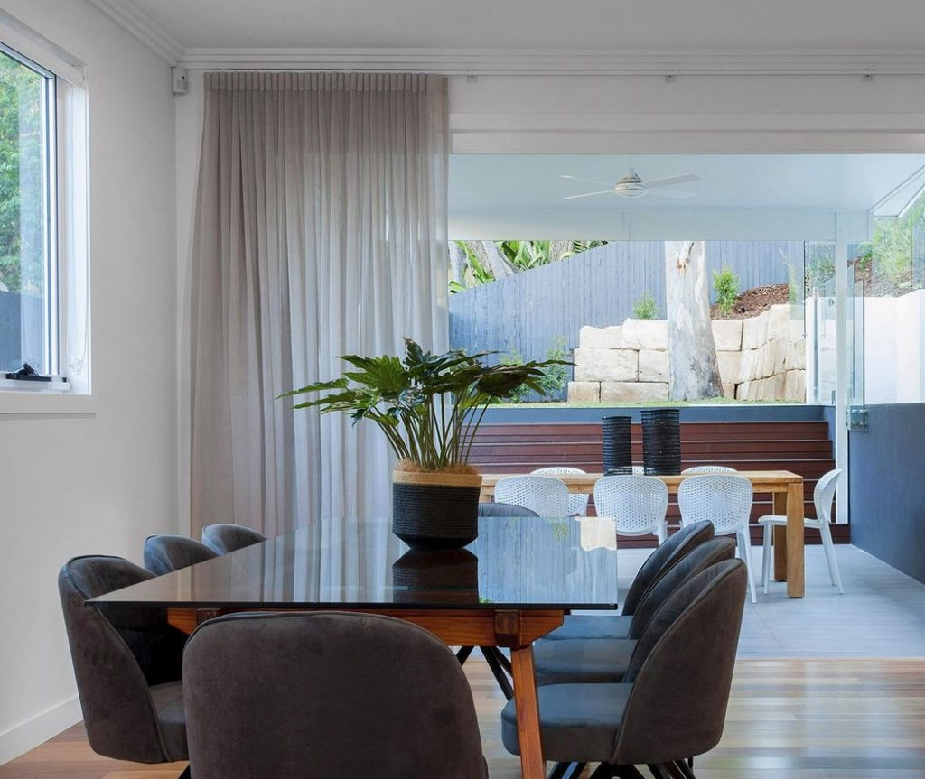 A modern dining room with curtains in windows | How to choose curtain colour blog post featured image.