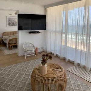 kayla boyd's living and entertainment room with a beach view and blind curtains in windows