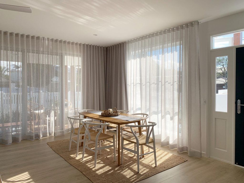 A modern dining room on a sunny day with small dining table surrounded by chairs and with Blindo curtains in the windows.