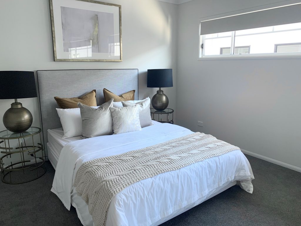 A modern bedroom wiht a large bed, stacked with pillows and blinds purchased online in the windows,