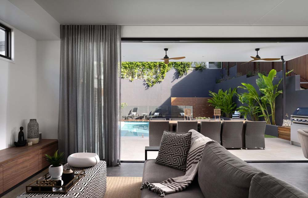 A stylish living, entertainment area next to a patio facing a pool with elegant curtains in view