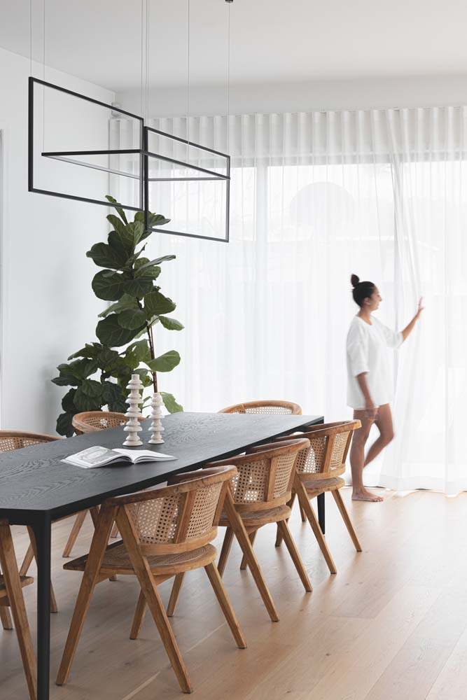 A woman pulling curtains across